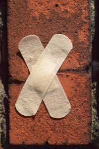 Bandages on crack in brick wall to represent credit repair