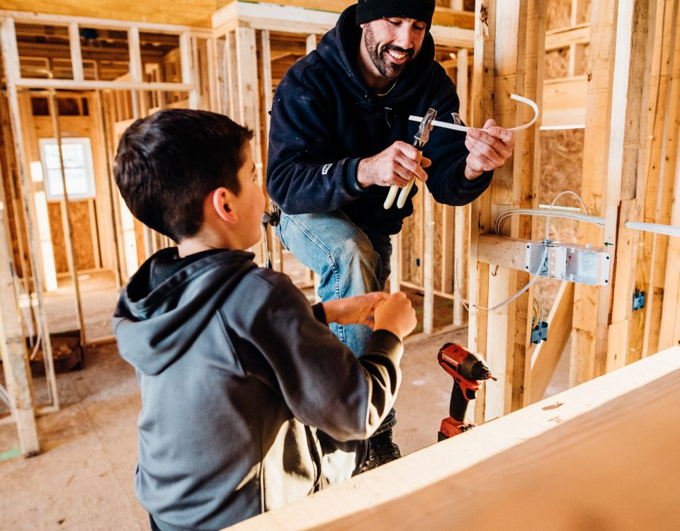 Boy and man building a house. Tradelines can help to build credit.