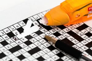 Filled-in crossword puzzle repaired with white-out. Repair credit by removing errors from your credit report.